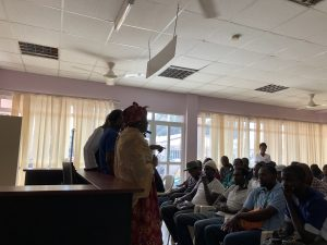 UNFPA's National Coordinator for FGM and Gender speaking with men at Bundung MCH Hospital's weekly male clinic.