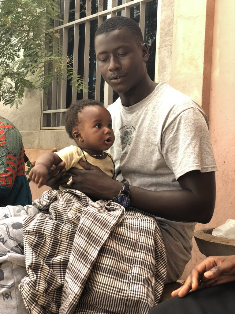 Man with baby at Bundung MCH Hospital following a male clinic. There were concurrent antenatal and postnatal visits occuring.