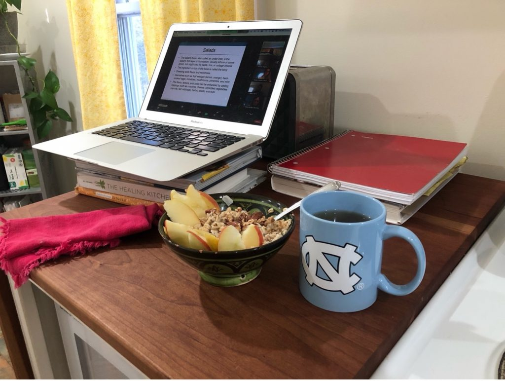 My work from home setup: complete with a makeshift standing desk, breakfast, and UNC memorabilia.
