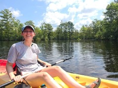Picture of Katie in a kayak on a lake.